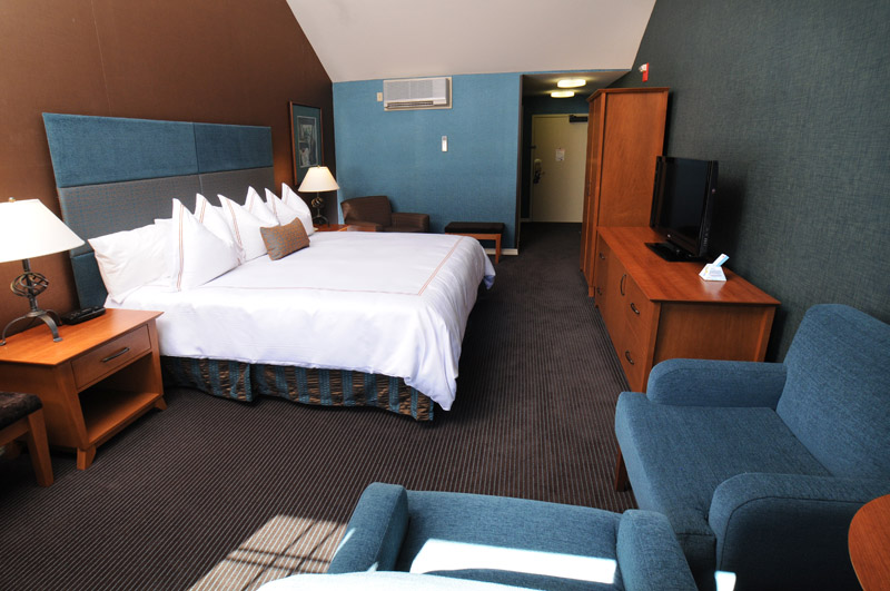 Verona King size suite room showing bed, arm chairs and view facing the room entrance.
