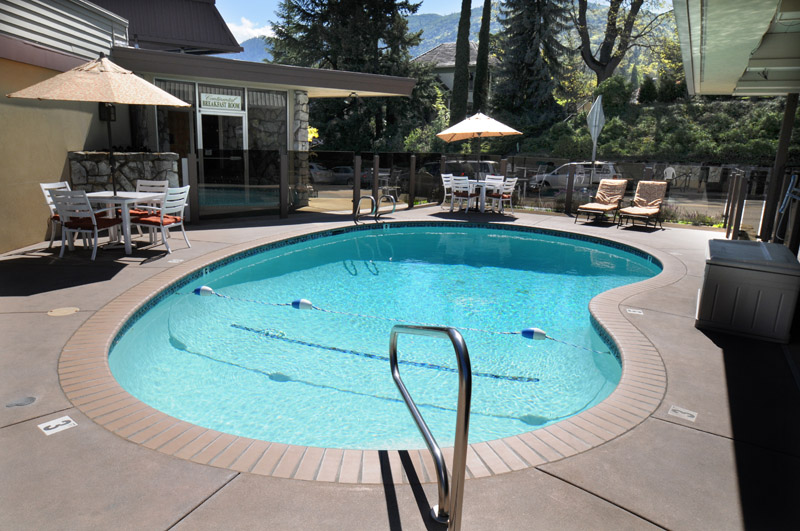 The Bard's Inn Hotel, kidney shaped pool, facing the street, pool furniture with sun umbrellas. Trees and hills in the background.